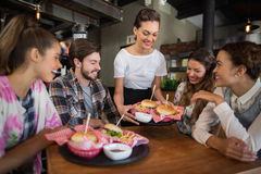 Waitress serving burgers to customers in restaurant. Young waitress serving burgers to customers in restaurant Stock Image