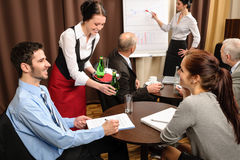 Waitress serving business people conference room Stock Photo