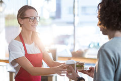 Waitress serving a coffee and sandwich to customer in café Stock Photography