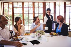 Waitress serving coffee on the table stock image