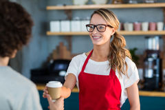 Waitress serving a coffee to customer at counter in café Royalty Free Stock Photography