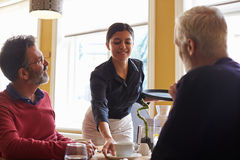 Waitress serving coffee to a male couple in a restaurant stock image