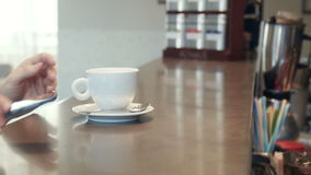 Waitress serving coffee to a man on a mobile. Phone passing the cup over the counter as he texts a message, close up of the hands stock video