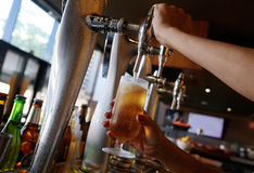 Waitress serving cold pressure beer Royalty Free Stock Photography