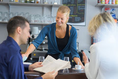 Waitress serving couple customers. A waitress serving a couple of customers Stock Images