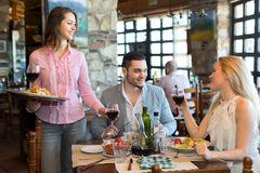 Waitress serving couple in a restaurant Royalty Free Stock Images