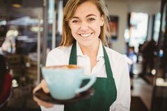 Waitress serving a cup of coffee Royalty Free Stock Image