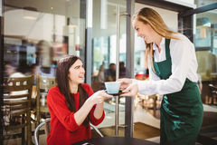 Waitress serving a cup of coffee Stock Photography