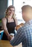 Waitress serving a cup of coffee and croissant to customer Royalty Free Stock Images