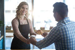 Waitress serving a cup of coffee and croissant to customer Royalty Free Stock Photos
