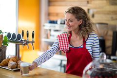 Waitress serving a cup of coffee to customer in café Stock Images