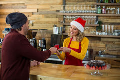 Waitress serving a cup of coffee to customer in café Royalty Free Stock Photo