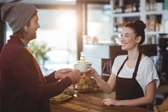 Waitress serving a cup of coffee to customer Royalty Free Stock Photos