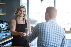 Waitress serving a cup of cold coffee to customer Royalty Free Stock Images