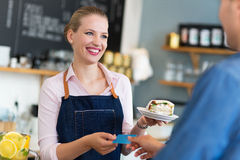 Waitress serving customer at the coffee shop Royalty Free Stock Photo