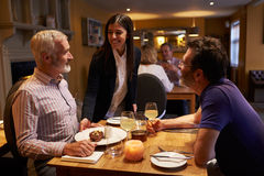 Waitress serving a dessert to a male couple in a restaurant Royalty Free Stock Photos