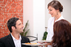 Waitress serving dishes Stock Images