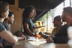 Waitress Serving Drinks To Group Of Male Friends Meeting In Sports Bar stock image