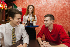 Waitress serving drinks to men in restaurant Royalty Free Stock Images