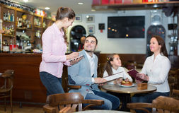 Waitress serving family of three Stock Images