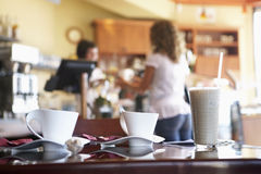Waitress serving female customer in cafe, focus on glass and coffee cups on table in foreground Royalty Free Stock Image