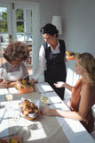 Waitress serving food to customers. In restaurant Royalty Free Stock Photos