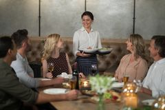 Waitress serving food to customers. In restaurant Stock Photo