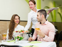 Waitress serving food to visitors. Charming waitress serving meal to visitors table royalty free stock image