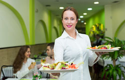 Waitress serving food to visitors Stock Photo