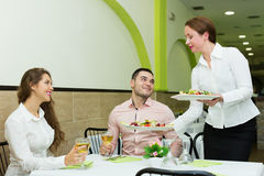 Waitress serving food to visitors Royalty Free Stock Photo