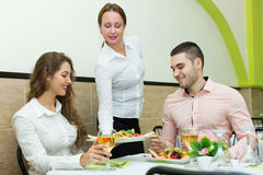 Waitress serving food to visitors Stock Photography