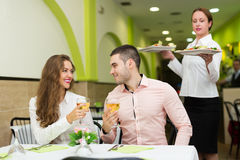 Waitress serving food to visitors Royalty Free Stock Photography