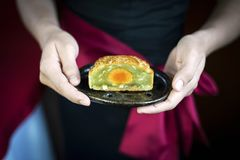 Waitress serving traditional chinese festive mooncake pastry des. Waitress serving gourmet traditional chinese festive mooncake pastry dessert Royalty Free Stock Photos