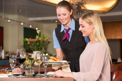 Waitress serving the meal to guest in restaurant Stock Image