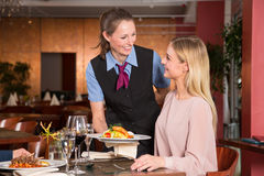 Waitress serving the meal to guest in restaurant Royalty Free Stock Image