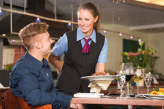 Waitress serving the meal to guest in restaurant. Waitress serving the meal to a guest in restaurant Stock Photos