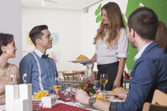 Waitress serving a meal to guests in restaurant Stock Images