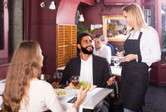 Waitress serving meal for young couple at table Stock Photo