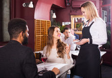 Waitress serving meal for young couple at table Royalty Free Stock Image