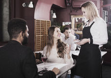 Waitress serving meal for young couple at table. Happy european waitress serving meal for young couple at table stock photos