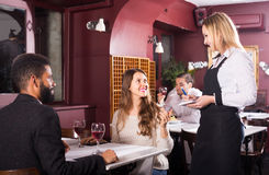 Waitress serving meal for young couple at table Stock Image