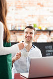 Young man being served at cafe Royalty Free Stock Images