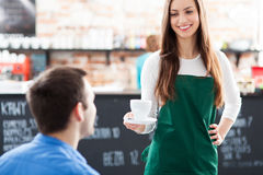 Waitress serving man coffee. Waitress serving men coffee at cafe Stock Photography