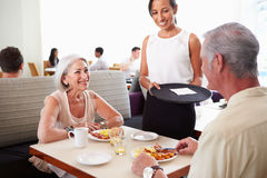 Waitress Serving Senior Couple Breakfast In Hotel Restaurant Royalty Free Stock Photos