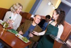 Waitress serving senior customers. Smiling young waitress serving senior customers at dinner in cafe Stock Photos