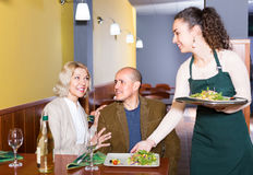Waitress serving senior customers. Smiling young waitress serving elderly couple at dinner in cafe Stock Photography