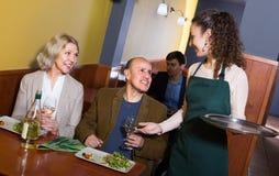Waitress serving senior customers Stock Photos