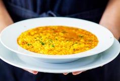 Spanish rice paella. Waitress serving a spanish seafood  paella dish Royalty Free Stock Photo