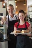 Waitress smiling at the camera showing cakes Royalty Free Stock Photo