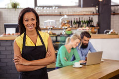 Waitress standing with arms crossed. In a cafe Royalty Free Stock Photography